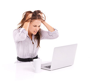 Frustrated businesswoman with a laptop in front of her - isolated on white