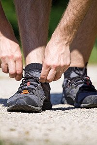 Trail runner in summer nature tying sport shoes